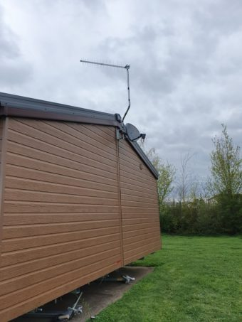 A new aerial and satellite dish onto a mobile home in persho…